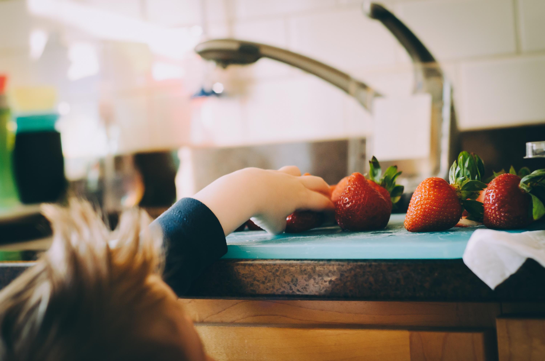 Egy kisgyerek a konyhapult felé nyújtózik, hogy onnan epret vegyen el