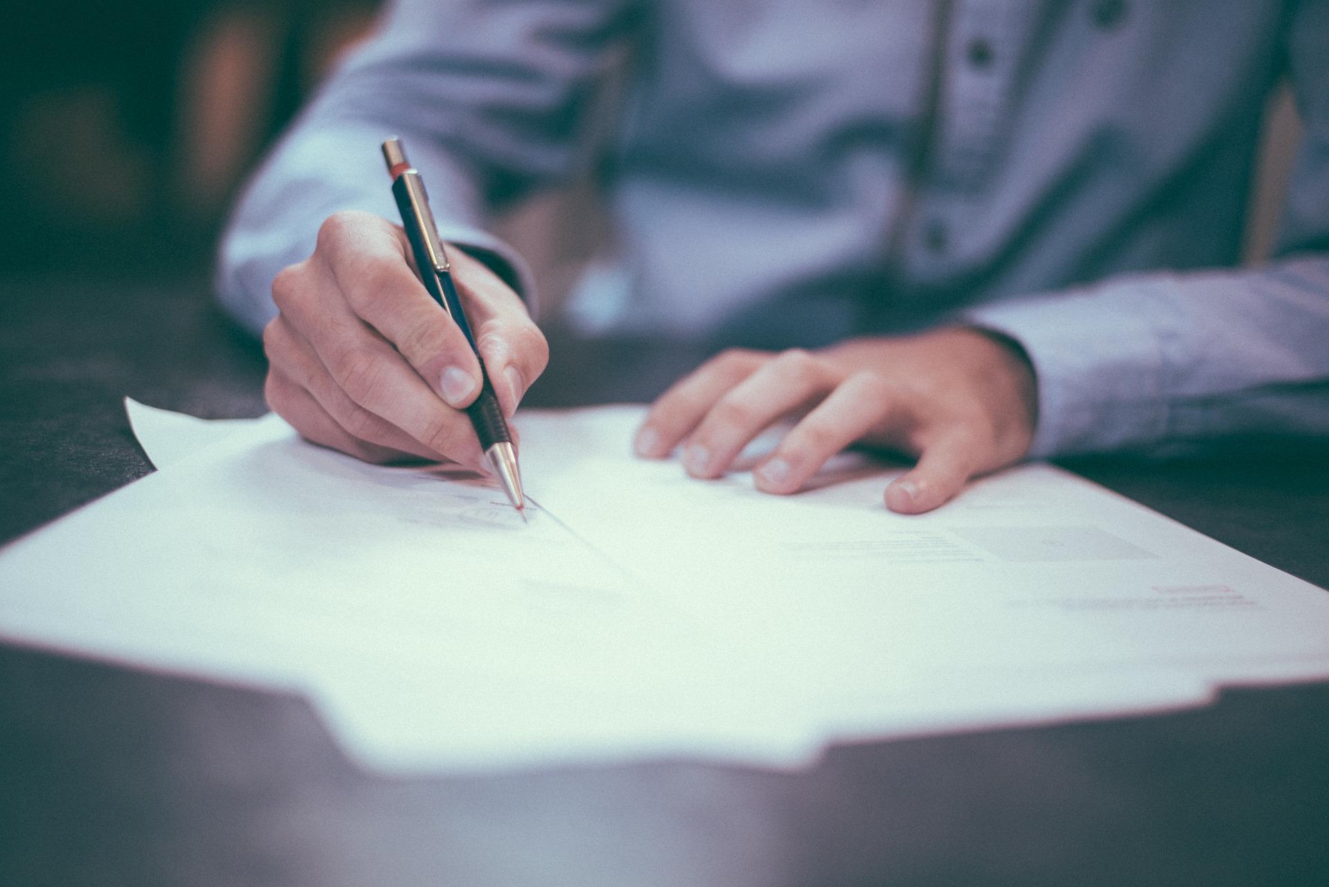 Egy férfi kezei, aki világos ingben tollal levelet ír