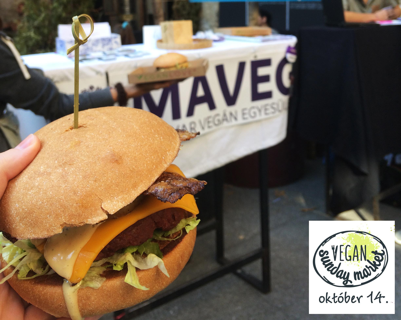 Egz kézben tartot vegán burger egy MAVEG-es molinóval lefedett asztal előtt.