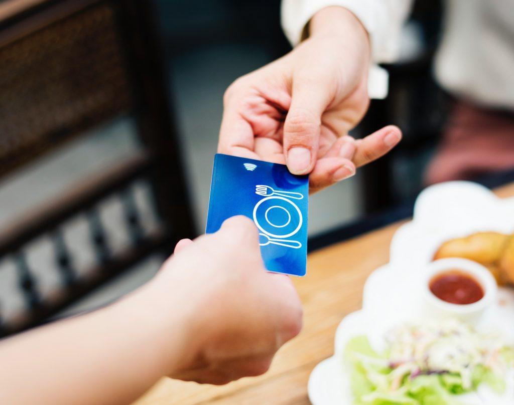 Bankkártyát nyújt egy személy egy másiknak