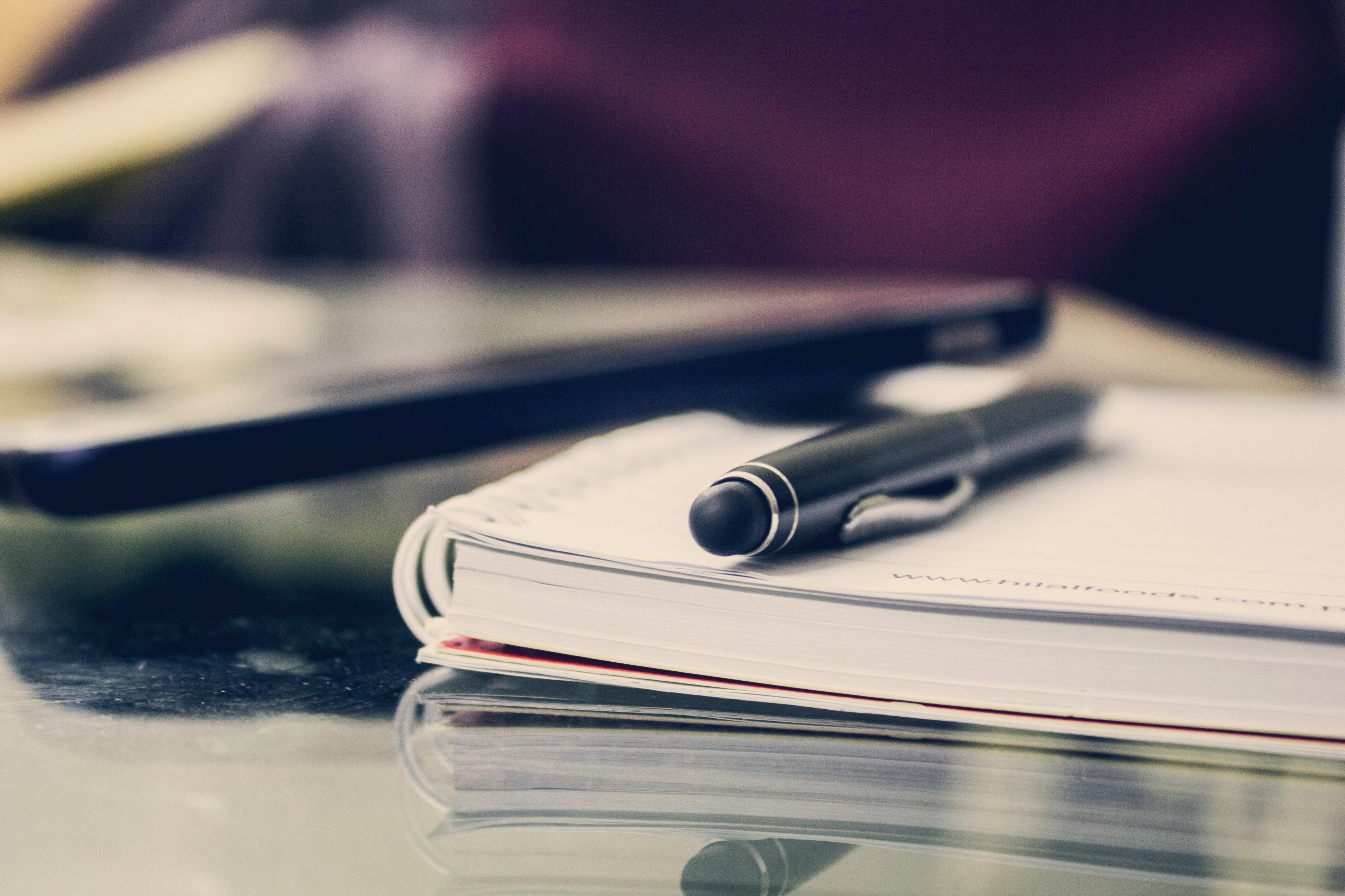 Fekete toll egy füzeten az asztalon
